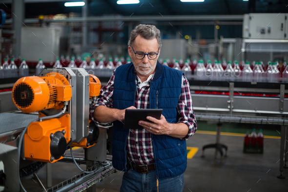 Factory Worker Using Digital Tablet Next To Production Line